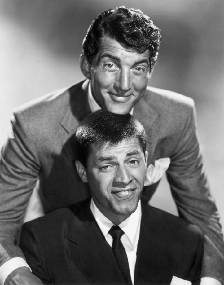 circa 1955: American comic team Dean Martin (1917 - 1995) and Jerry Lewis smiling in a promotional portrait. Martin smiles and rests his chin on top of Lewis's head, as Lewis makes a funny face.